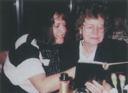 <em>Mary Ellen and Kathleen share family photographs on the night they were reunited.</em>