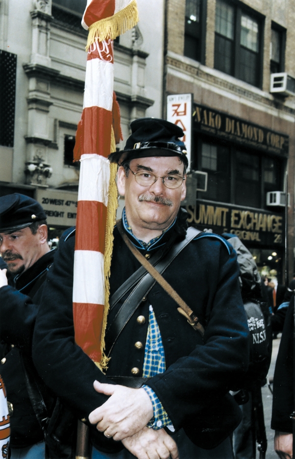 <em>During the Parade, Stephan O'Neill removes his eyeglasses, which are not authentic Civil War era. Carrying the American flag, he marches blind, he says.</em>