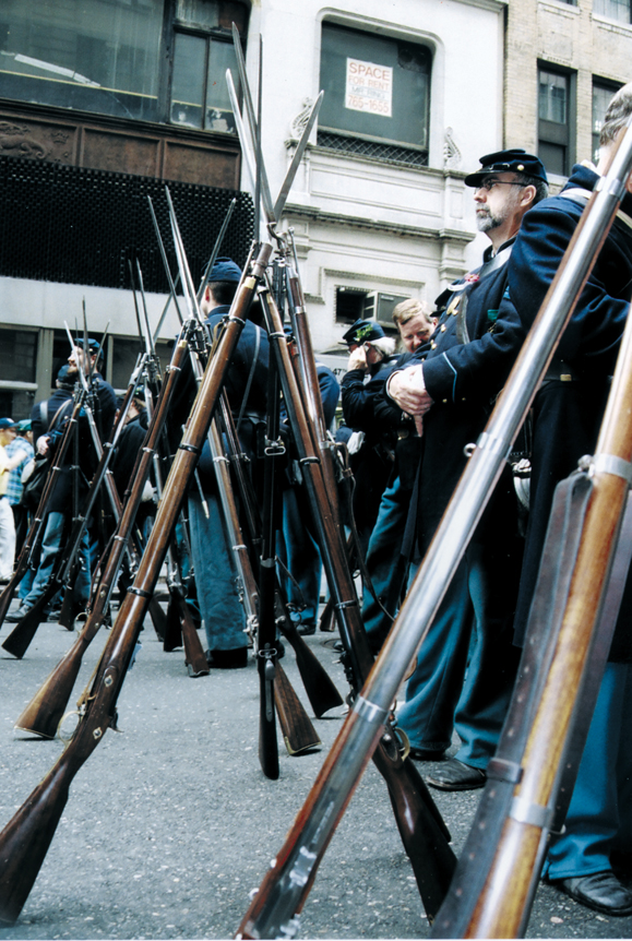 <em>Re-enactors give their muskets a rest while waiting to join the parade.</em>